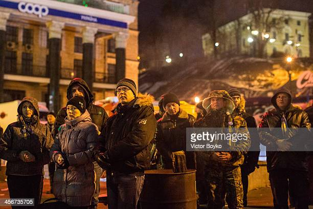 Protesters watch the TV screen on Maidan Square as protests continue on December 14 2013 in Kiev Ukraine Antigovernment protests began three weeks...