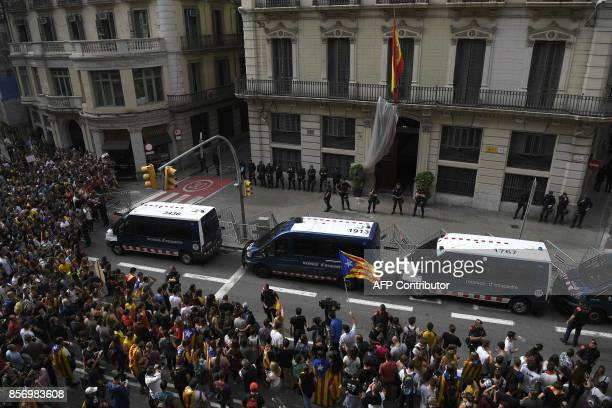 Protesters wave a Catalan proindependence 'Estelada' flag as they gather outside the Spanish police headquarters in Barcelona as part of a general...
