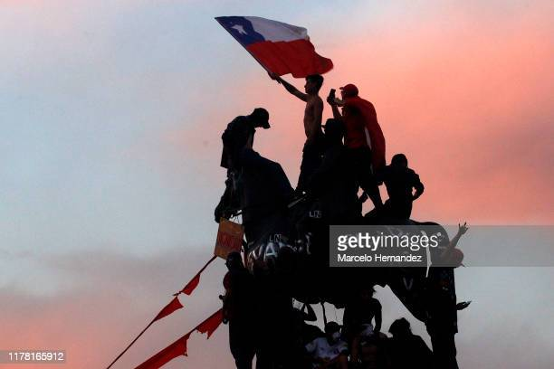 Protesters wave a Chilean flag during the eighth day of protests against President Sebastian Piñera's government on October 25 2019 in Santiago Chile...