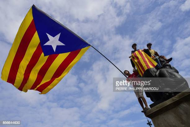 Protesters wave a giant Catalan proindependence 'Estelada' flag atop a sculpture during a demonstration in Barcelona on October 2 2017 a day after...