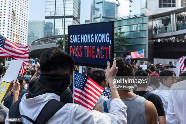Protesters wave American flags while carrying a placard urging the USA to enact the Hong Kong Human Rights Act during the demonstration. Thousands of...