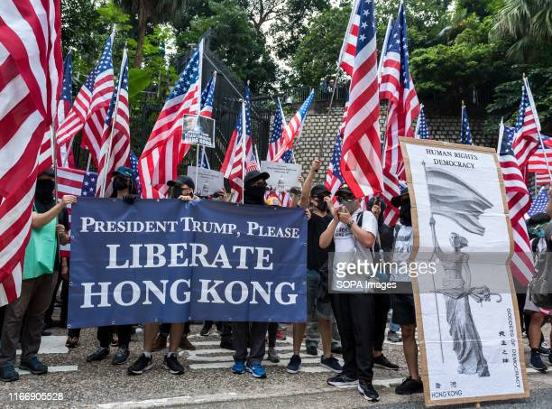 Protesters wave American flags while carrying placards urging the USA to enact the Hong Kong Human Rights Act during the demonstration Thousands of...
