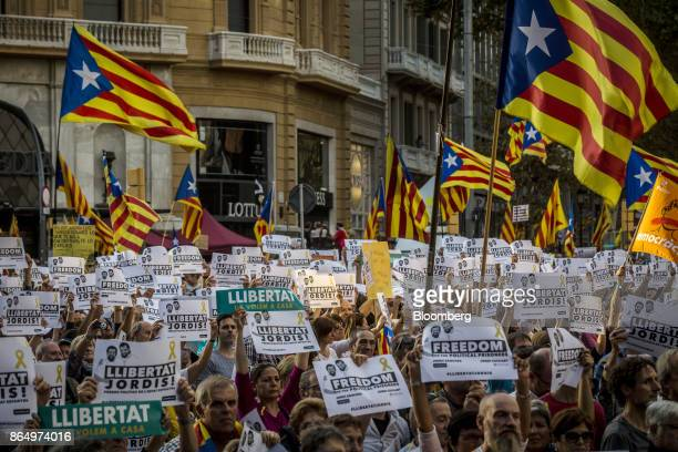 Protesters wave Catalan flags and hold signs during a demonstration against the Spanish government and the imprisonment of separatist leaders Jordi...