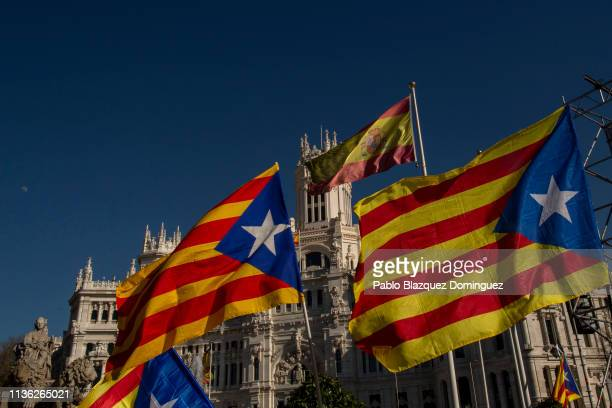Protesters wave Catalan Independence flags as a Spanish flag waves in the air at Cibeles Square before a demonstration titled 'Self-determination is...