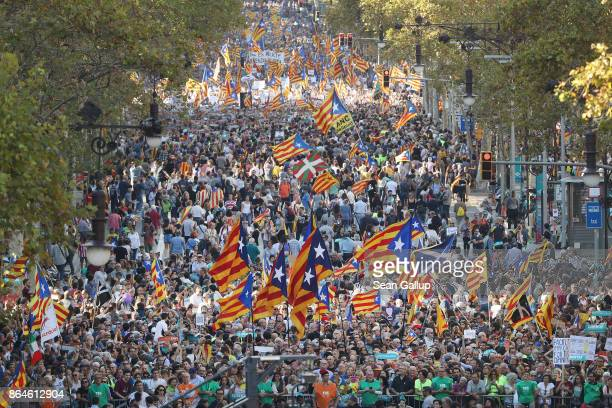 Protesters wave Catalan independence flags as they demonstrate against the Spanish federal government's move to suspend Catalonian autonomy and...