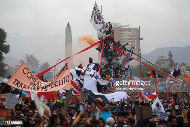 Protesters wave Chilean flags and climb the monument to General Baquedano during the eighth day of protests against President Sebastian Piñera's...