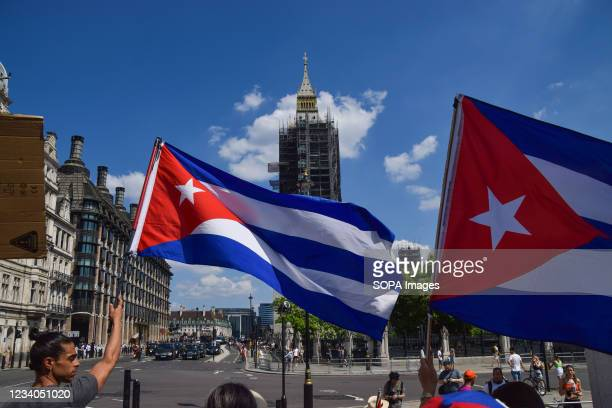Protesters wave Cuban flags during the SOS Cuba demonstration. Demonstrators gathered in Parliament Square as part of the ongoing worldwide protests...