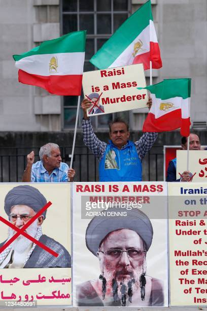 Protesters wave flags and stand behind banners during a demonstration organised by supporters of the National Council of Resistance of Iran to...