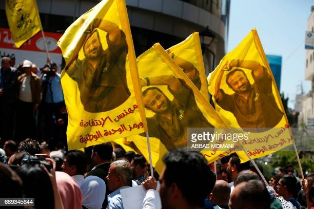 Protesters wave flags bearing a portrait of prominent jailed Palestinian Marwan Barghouti during a rally in the West Bank city of Ramallah to show...