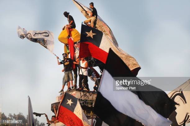 Protesters wave flags in a demonstration against Chilean President Sebastian Piñera the 50th consecutive day of unrest on December 06 2019 in...