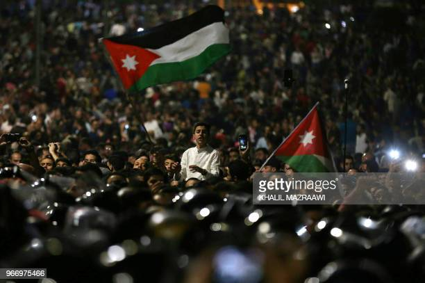 Protesters wave flags near Jordanian security forces during a demonstration outside the prime minister's office in the capital Amman late on June 3...