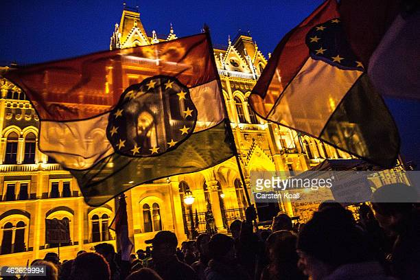 Protesters wave flags with a combination with the Hungarian national colors and the symbol of the European Union as several thousand protesters...