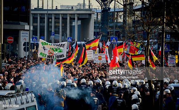 Protesters wave German flags alongside a banner saying 'Rapefugees Not Welcome' as supporters of Pegida Hogesa and other rightwing populist groups...