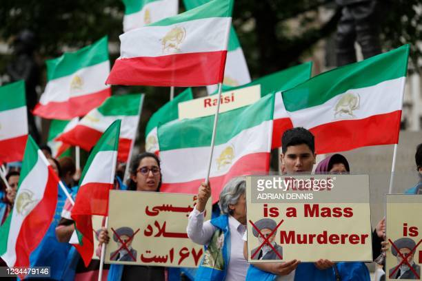 Protesters wave Iranian opposition flags and hold banners during a demonstration organised by supporters of the National Council of Resistance of...