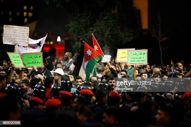 Protesters wave Jordanian national flags and hold banners during a demonstration against a draft income tax law near the prime minister's office in...