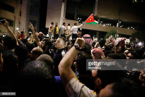 Protesters wave Jordanian national flags and illuminate their mobile phones during a demonstration against a draft income tax law near the prime...