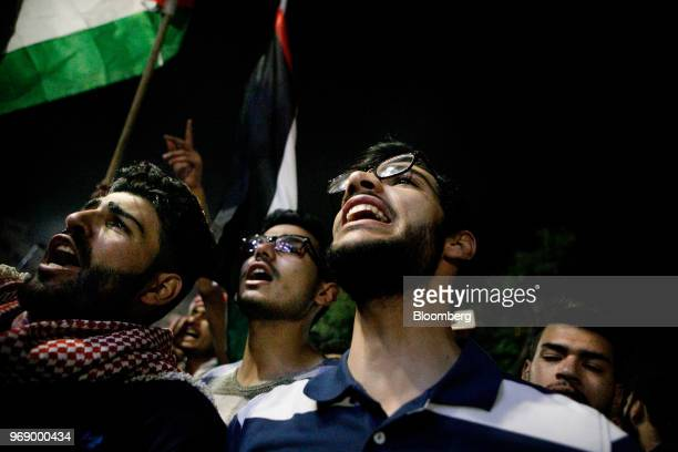 Protesters wave Jordanian national flags and shout during a demonstration against a draft income tax law near the prime minister's office in Amman...