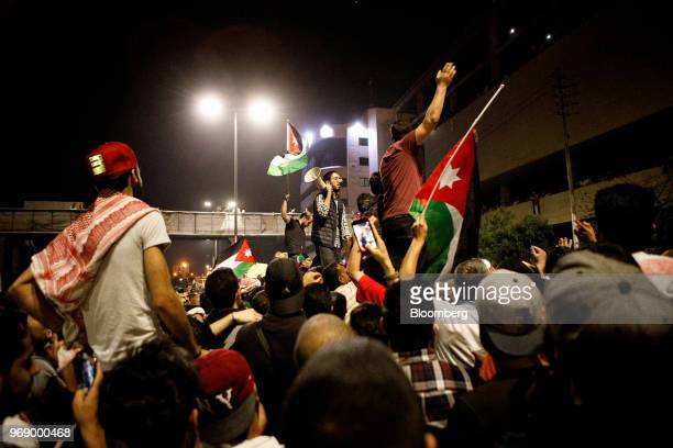 Protesters wave Jordanian national flags and shout slogans during a demonstration against a draft income tax law near the prime minister's office in...