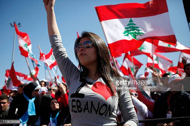 Protesters wave Lebanese flags during a demonstration on March 13 2011 in Beirut Lebanon Tens of thousands of Lebanese opposition supporters demanded...