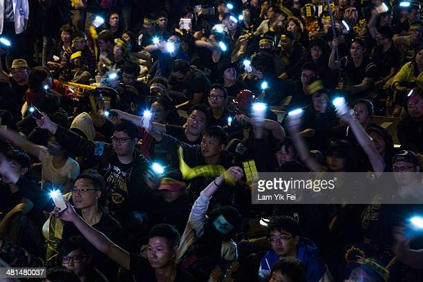Protesters wave mobile phones as over two hundred thousand people rally on March 30 2014 in Taipei Taiwan Taiwanese student protesters opposing the...