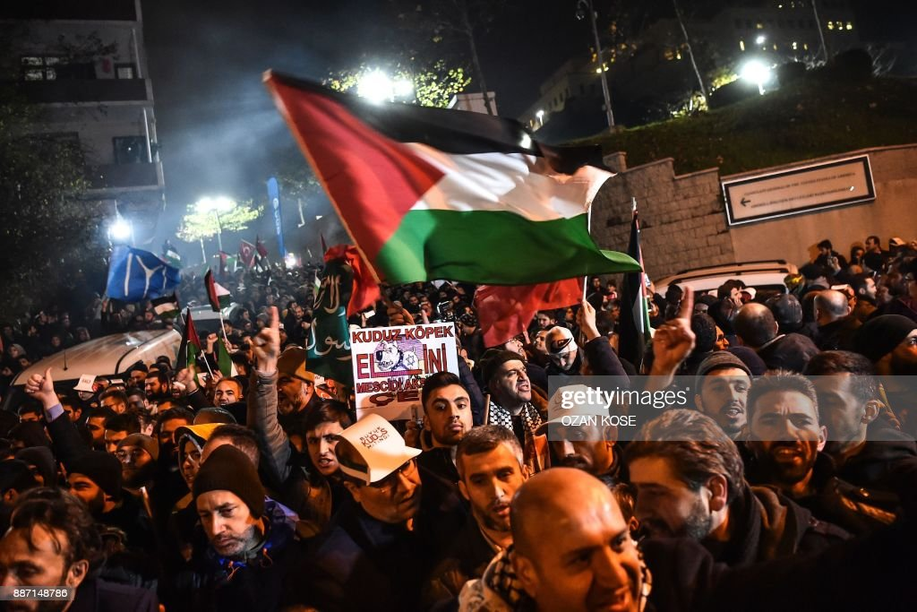 Protesters wave Palestinian and Turkish flags during a demonstration against the US and Israel in front of the US consulate in Istanbul on December 6, 2017. Hundreds of people staged a protest outside the US consulate in Istanbul angrily denouncing the US president's move to recognise Jerusalem as the capital of Israel. Around 1,500 people gathered outside the well-protected compound close to the Bosphorus which was sealed off by police with barricades, an AFP correspondent said. /