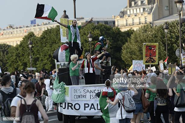 Protesters wave Palestinian flags as they stand on a vehicle during a demonstration on July 23 2014 in front of the Invalides in Paris to denounce...