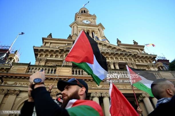 Protesters wave Palestinian flags during a demonstration against Israel at the Town Hall in Sydney on May 15 amid the ongoing conflict between Israel...