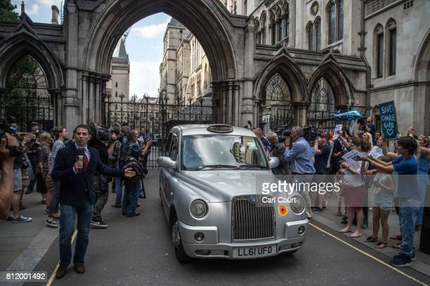Protesters wave placards as a taxi carrying Chris Gard and Connie Yates the parents of terminally ill toddler Charlie Gard leaves the High Court on...