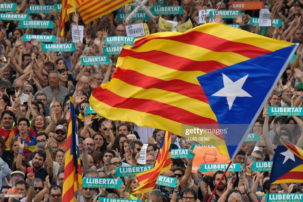 Protesters wave pro-independence Catalan Estelada flags during a demonstration in Barcelona on October 21, 2017 in support of separatist leaders Jordi Sanchez and Jordi Cuixart, who have been detained pending an investigation into sedition charges. Spain announced that it will move to dismiss Catalonia's separatist government and call fresh elections in the semi-autonomous region in a bid to stop its leaders from declaring independence. /