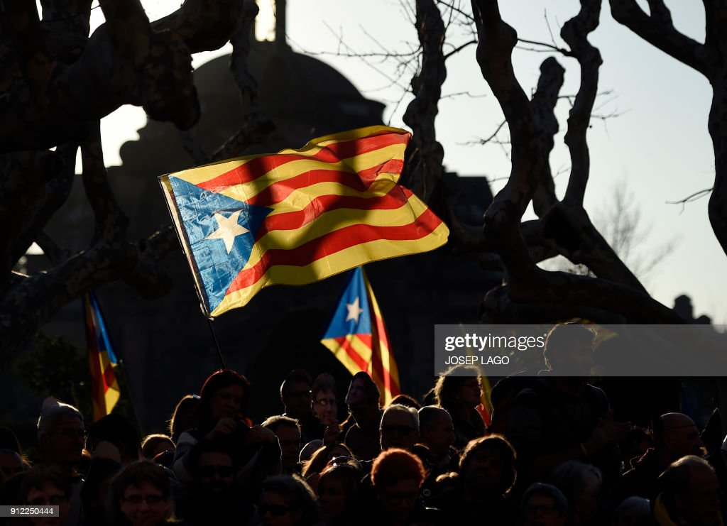 TOPSHOT - Protesters wave pro-independence Catalan flag during a demonstration outside the Catalan parliament on January 30, 2018 in Barcelona. The speaker of Catalonia's parliament Roger Torrent delayed a key debate in the regional assembly on ousted separatist leader Carles Puigdemont's bid to form a new government, but defended his right to return to power. / AFP PHOTO / Josep LAGO