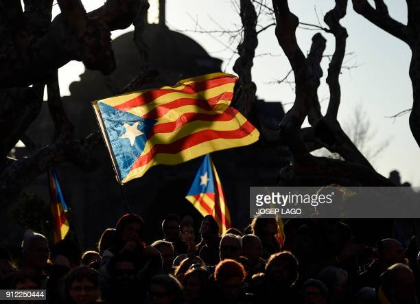 TOPSHOT Protesters wave proindependence Catalan flag during a demonstration outside the Catalan parliament on January 30 2018 in Barcelona The...