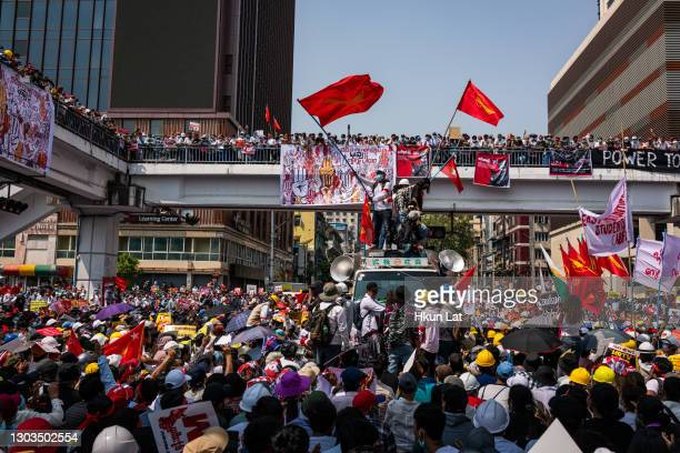 Protesters wave red NLD flags at Sule Square on February 22, 2021 in downtown Yangon, Myanmar. Armored vehicles continued to be seen on the streets...