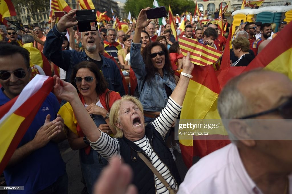 Protesters wave Spanish and Catalan flags during a demonstration called by Catalan Civil Society under the motto 'Catalonia yes, Spain too' in Barcelona on October 12, 2017. Spain marks its national day today with a show of unity in the face of Catalan independence efforts, a day after the central government gave the region's separatist leader a deadline to abandon his secession bid. The country is suffering its worst political crisis in a generation after separatists in the wealthy northeastern region voted in a banned referendum on October 1 to split from Spain GUERRERO