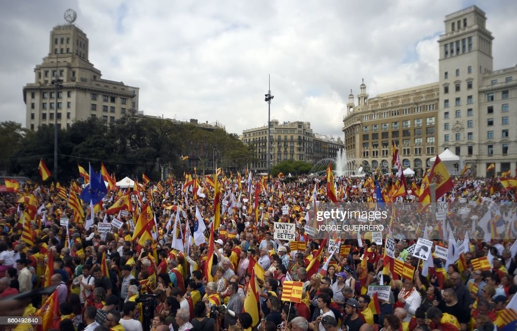 TOPSHOT - Protesters wave Spanish and Catalan flags during a demonstration called by Catalan Civil Society under the motto 'Catalonia yes, Spain too' in Barcelona on October 12, 2017. Spain marks its national day today with a show of unity in the face of Catalan independence efforts, a day after the central government gave the region's separatist leader a deadline to abandon his secession bid. The country is suffering its worst political crisis in a generation after separatists in the wealthy northeastern region voted in a banned referendum on October 1 to split from Spain GUERRERO