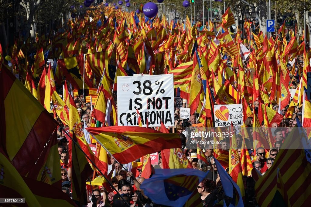Protesters wave Spanish and Catalan Senyera flag while holding a sign reading '38 percent is not Catalonia' in reference to a referendum voter turnout during a pro-unity demonstration in Barcelona on October 29, 2017. Pro-unity protesters were to gather in Catalonia's capital Barcelona, two days after lawmakers voted to split the wealthy region from Spain, plunging the country into an unprecedented political crisis. /