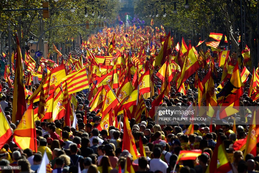 TOPSHOT - Protesters wave Spanish and Catalan Senyera flags during a pro-unity demonstration in Barcelona on October 29, 2017. Pro-unity protesters were to gather in Catalonia's capital Barcelona, two days after lawmakers voted to split the wealthy region from Spain, plunging the country into an unprecedented political crisis. /