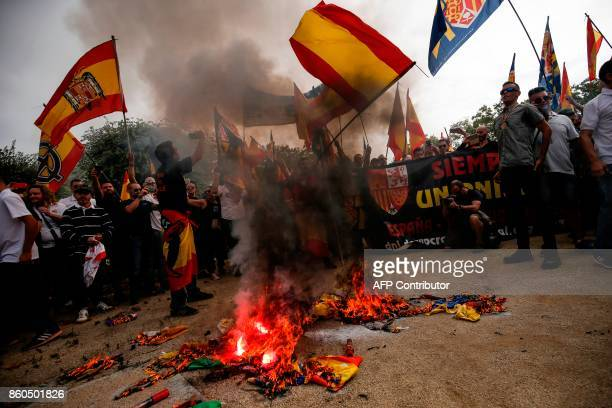 Protesters wave spanish flags as they burn 'Estelada' Catalan proindependence flags during an ultraright wing antiseparatist demonstration for the...