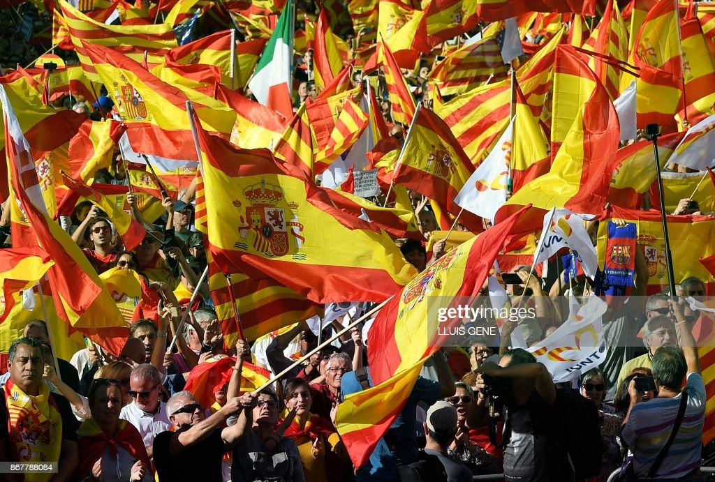 Protesters wave Spanish flags during a pro-unity demonstration in Barcelona on October 29, 2017. As many as one million Spaniards rallied in Catalonia's capital Barcelona, waving national and European flags and chanting 'Viva Espana!' to denounce regional lawmakers' vote to sever the region from Spain. /