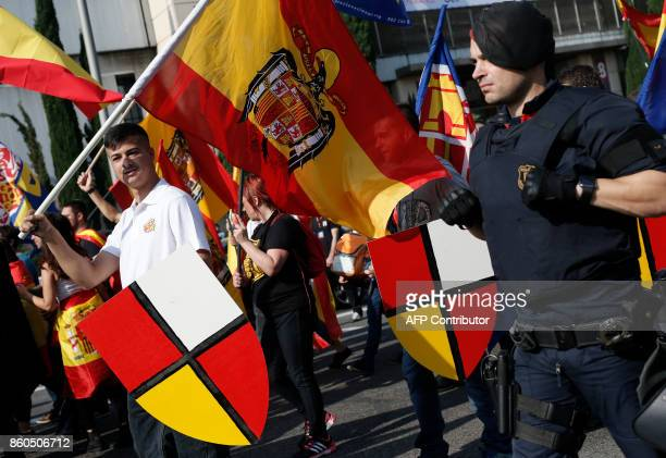 Protesters wave Spanish preconstitutional flags as they march during an ultraright wing antiseparatist demonstration for the unity of Spain called by...
