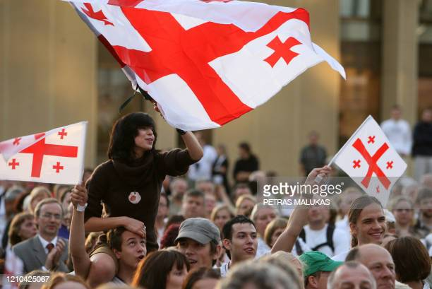 Protesters wave the Georgian flag as they marched from the Vilnius Cathedral to Parliament Square here on August 13 2008 to support Georgia in the...