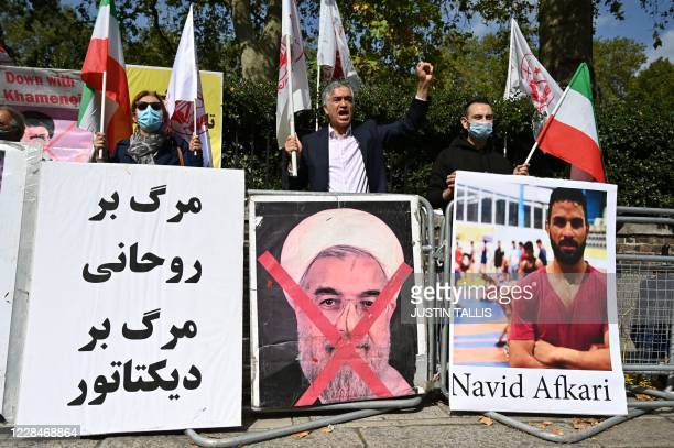 Protesters wave the Lion and Sun flag of the National Council of Resistance of Iran and the white flag of the People's Mujahedin of Iran two Iranian...