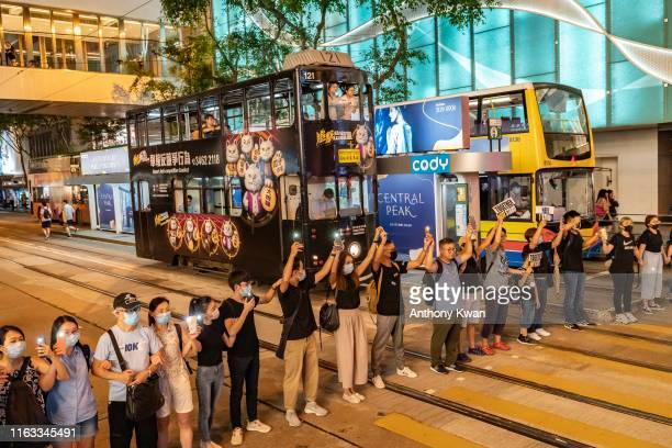 Protesters wave their cellphones and hold hands to form a human chain as they take part in an anti-government rally in Central district on August 23,...