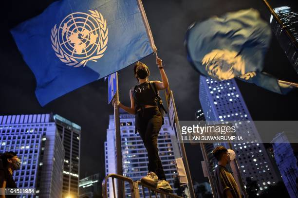 TOPSHOT Protesters wave United Nations flags at a #MeToo rally in Hong Kong on August 28 to protest alleged sexual assaults by police against...