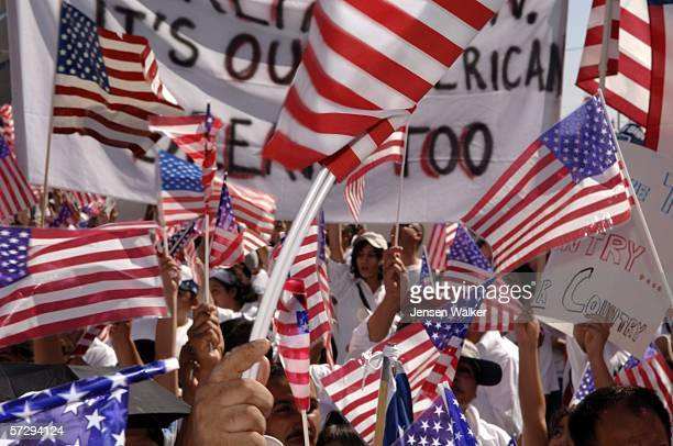 Protesters wave US Flags and banners as they participate in the Mega March on City Hall April 9 2006 in Dallas Texas According to reports an...