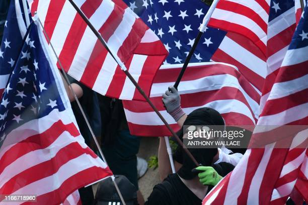 Protesters wave US national flags as they march from Chater Garden to the US consulate in Hong Kong on September 8 to call on the US to pressure...