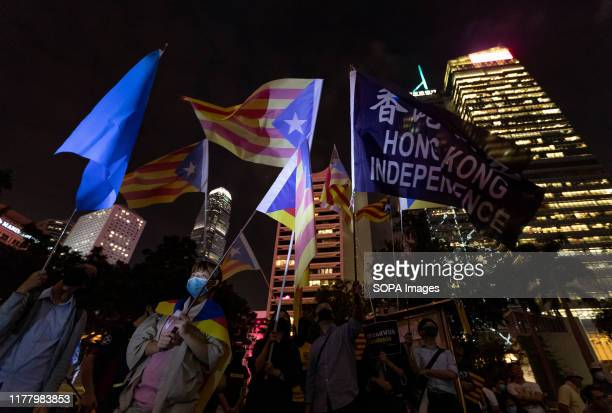 Protesters waving Catalonia and Hong Kong Independence flags during the demonstration Hundreds of masked protesters gathered at Charter Garden in...