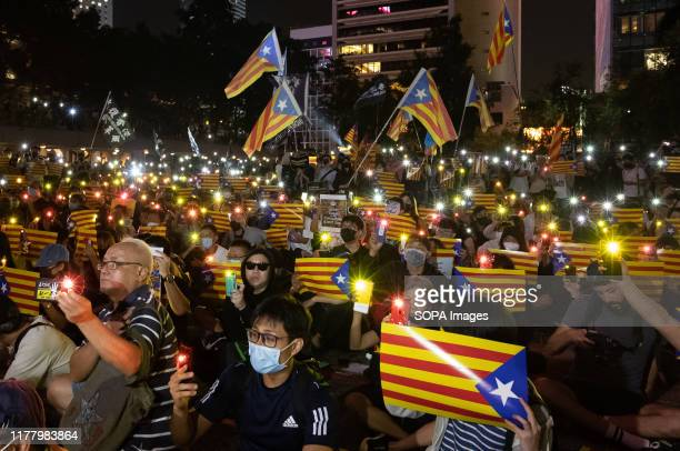 Protesters waving Catalonia flags during the demonstration Hundreds of masked protesters gathered at Charter Garden in Central to show solidarity...