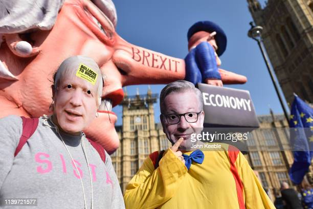 Protesters wear Boris Johnson and Michael Gove masks outside the Houses of Parliament on April 01 2019 in London England MPs in Parliament will vote...