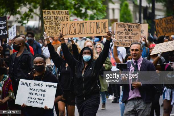 Protesters wear face masks as they attend the Black Lives Matter movement march through central London from Hyde Park to Parliament Square following...