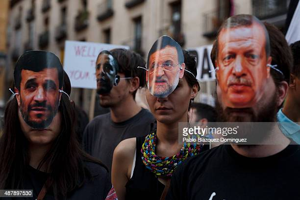 Protesters wear masks depicting 'Former Iranian President Mahmoud Ahmadinejad' 'US President Barack Obama' 'Spanish Prime Minister Mariano Rajoy' and...